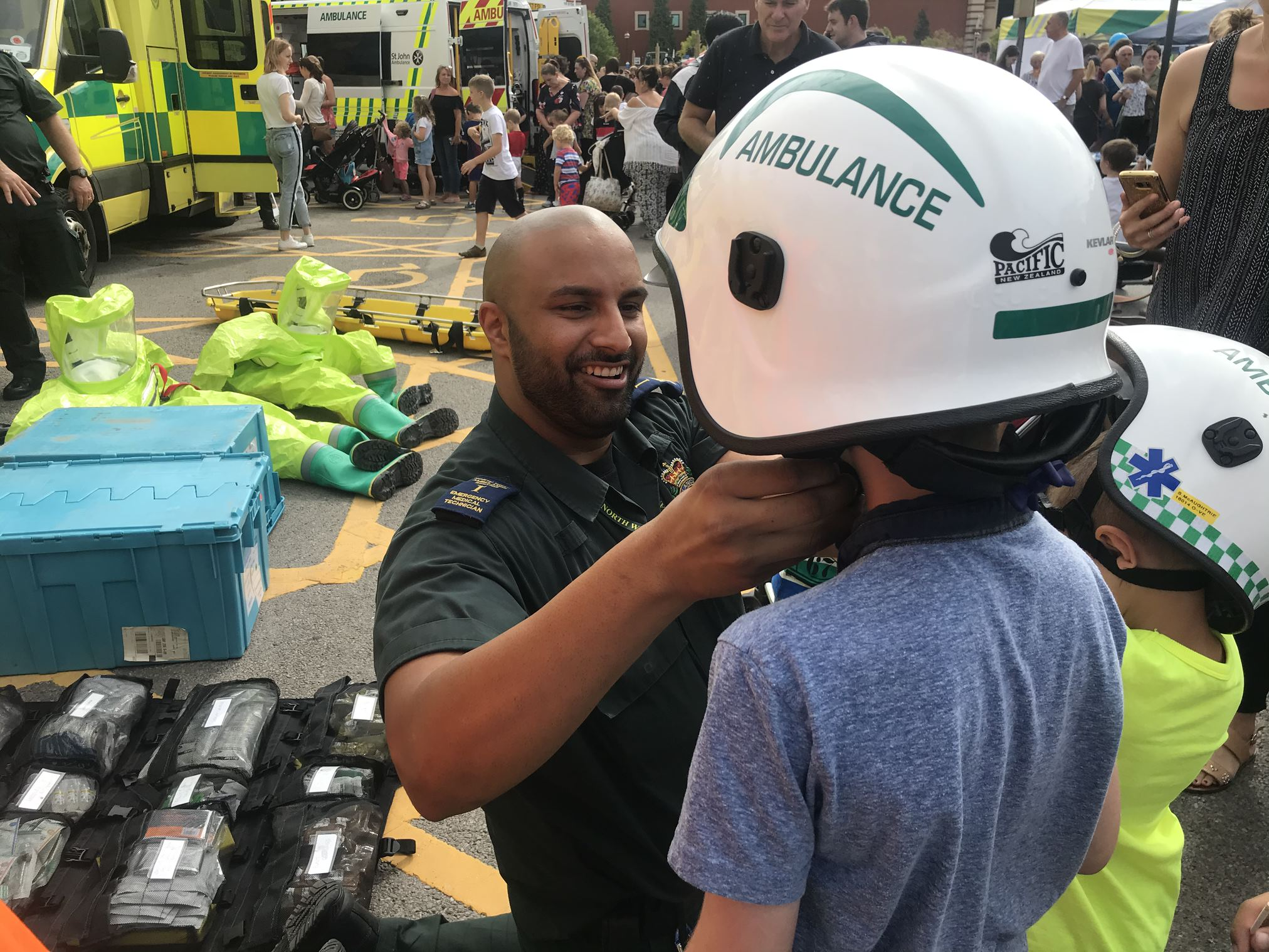 Paramedic helping young kids understand ambulance equipment.