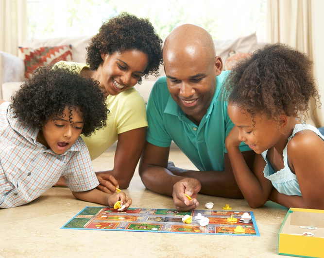 Young family playing a board game together.